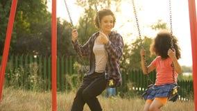 Δύο εύθυμες αδελφές που ταλαντεύονται μαζί στην υπαίθρια παιδική χαρά παιδιών, ευτυχία στοκ εικόνα με δικαίωμα ελεύθερης χρήσης