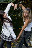 Δύο εύθυμες γυναίκες που κάνουν τη μορφή καρδιών με τα χέρια Στοκ φωτογραφίες με δικαίωμα ελεύθερης χρήσης