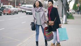 Δύο ελκυστικές γυναίκες αφροαμερικάνων με τις αγορές τοποθετούν την απαίτηση του αμαξιού ταξί σε σάκκο επιστρέφοντας από τις πωλή απόθεμα βίντεο