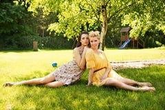 Δύο ελκυστικές γυναίκες που στηρίζονται στο λιβάδι λουλουδιών Στοκ Φωτογραφία