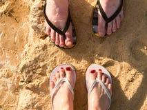 Δύο ζευγάρια των αρσενικών και θηλυκών ποδιών με ένα μανικιούρ στις παντόφλες, ένα πόδι με τα δάχτυλα στις σαγιονάρες σε ένα αμμώ στοκ φωτογραφία με δικαίωμα ελεύθερης χρήσης