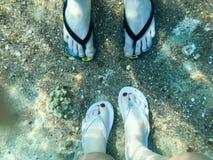 Δύο ζευγάρια των αρσενικών και θηλυκών ποδιών στις παντόφλες, πόδια με τα δάχτυλα στις σαγιονάρες κάτω από το νερό, υποβρύχια άπο Στοκ Εικόνες