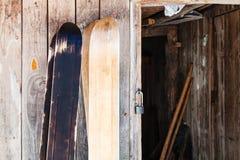 δύο ζευγάρια των ευρέων δασικών σκι κοντά στο ξύλινο υπόστεγο στοκ φωτογραφίες