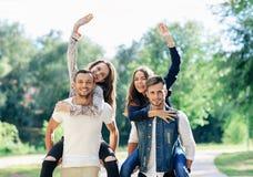 Δύο ζευγάρια των νέων στο πάρκο, κορίτσια κυματίζουν στοκ εικόνα
