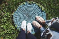 Δύο ζευγάρια των ποδιών γυναικών ` s στην καταπακτή Στοκ Εικόνες