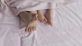 Δύο ζευγάρια των ποδιών της οικογένειας στο κρεβάτι κάτω από το coverlet - μητέρα και μωρό φιλμ μικρού μήκους