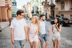 Δύο ζεύγη περπατούν στην οδό Ο τύπος στα γυαλιά και το ξανθό κορίτσι περπατά στο μέτωπο Εξετάζουν κάθε έναν Στοκ Εικόνα