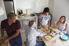 Δύο ζεύγη που προετοιμάζουν τα τρόφιμα και που πίνουν το κρασί, ανυψωμένη άποψη Στοκ Φωτογραφία