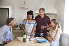 Δύο ζεύγη που προετοιμάζουν τα τρόφιμα και που πίνουν το κρασί, μπροστινή άποψη Στοκ Φωτογραφία