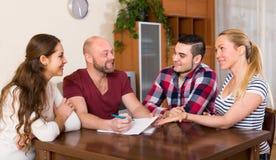 Δύο ζεύγη που συζητούν και που χαμογελούν Στοκ Εικόνες