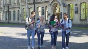 Δύο ζεύγη των ευτυχών σπουδαστών που περπατούν κοντά στο κολλέγιο και που μιλούν, ξένοιαστη νεολαία φιλμ μικρού μήκους