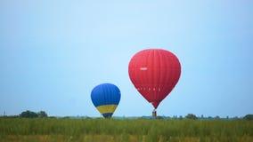 Δύο ζωηρόχρωμα μπαλόνια ζεστού αέρα που προετοιμάζονται για την ήπια προσγείωση, ακραίος αθλητισμός φιλμ μικρού μήκους