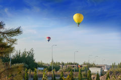 Δύο ζωηρόχρωμα μπαλόνια ζεστού αέρα που πετούν στα προάστια Στοκ φωτογραφία με δικαίωμα ελεύθερης χρήσης