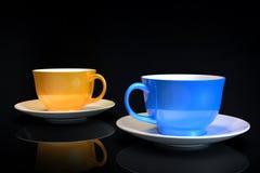 Δύο ζωηρόχρωμα φλιτζάνια του καφέ στο σκοτεινό υπόβαθρο στοκ εικόνες