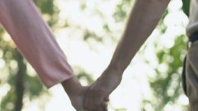 Δύο ηλικιωμένοι άνθρωποι που κρατούν τα χέρια και που περπατούν στο ελαφρύ υπόβαθρο, ευτυχές μέλλον απόθεμα βίντεο