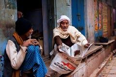 Δύο ηλικίας άτομα συζητούν τις πιό πρόσφατες ειδήσεις και διαβάζουν την εφημερίδα Στοκ Εικόνα