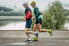 Δύο ηλικιωμένα joggers που οργανώνονται κατά μήκος του αναχώματος του ποταμού Στοκ φωτογραφίες με δικαίωμα ελεύθερης χρήσης