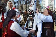 Δύο ηλικιωμένες γυναίκες με τα παραδοσιακά λαϊκά κοστούμια βοηθούν ένα νέο κορίτσι με τη μάσκα kuker της στοκ φωτογραφία