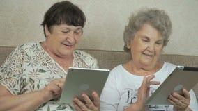 Δύο ηλικιωμένες γυναίκες που κρατούν τις ασημένιες ψηφιακές ταμπλέτες απόθεμα βίντεο