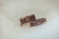 Δύο θαυμάσια γαμήλια δαχτυλίδια διαμαντιών στο άσπρο υπόβαθρο άνδρας αγάπης φιλιών έννοιας στη γυναίκα Στοκ Φωτογραφία