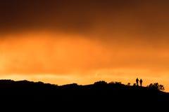 Δύο θεατές που στέκονται σε ένα ηλιοβασίλεμα προσοχής κορυφών υψώματος στοκ εικόνες