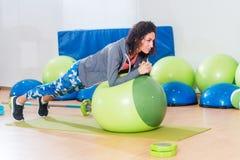 Δύο θετικές γυναίκες που κάνουν την άσκηση σανίδων που βρίσκεται στη σφαίρα ισορροπίας στη γυμναστική στοκ φωτογραφίες