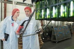 Δύο θετικοί εργαζόμενοι στα άσπρα παλτά στο εργοστάσιο ζυθοποιείων μπύρας Στοκ εικόνες με δικαίωμα ελεύθερης χρήσης