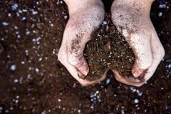 Δύο θηλυκά χέρια που κρατούν τη γη στα χέρια του Στοκ Εικόνες