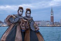 Δύο θηλυκές μάσκες στο κοστούμι, στο νησί SAN Giorgio, με το τετράγωνο σημαδιών του ST και τον πύργο κουδουνιών πίσω Στοκ εικόνες με δικαίωμα ελεύθερης χρήσης