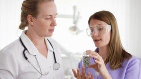 Δύο θηλυκοί γιατροί με την ταμπλέτα που συζητούν τη νέα επεξεργασία στο δωμάτιο νοσοκομείων Μπουκάλι εκμετάλλευσης των χαπιών απόθεμα βίντεο