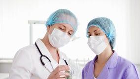Δύο θηλυκοί γιατροί στις ιατρικές μάσκες που συζητούν τη νέα επεξεργασία στο δωμάτιο νοσοκομείων Μπουκάλι εκμετάλλευσης των χαπιώ απόθεμα βίντεο