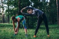 Δύο θηλυκοί δρομείς που κάνουν το κάμπτοντας τέντωμα ασκήσεων προθέρμανσης πίσω και τους μυς ποδιών πρίν τρέχει στο πάρκο στοκ φωτογραφία
