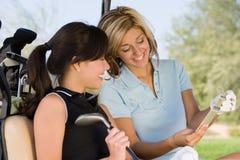 Δύο θηλυκοί παίκτες γκολφ που διαβάζουν τις σημειώσεις στο κάρρο γκολφ Στοκ Φωτογραφίες