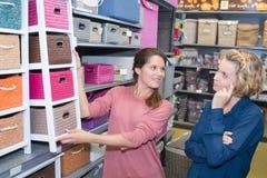 Δύο θηλυκοί πελάτες που αγοράζουν τα καλάθια στη μπουτίκ Στοκ Φωτογραφία