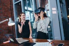 Δύο θηλυκοί υπεύθυνοι για την ανάπτυξη εφαρμογής που εξετάζουν νέο app που σχεδιάζεται για την κάσκα VR που στέκεται στο σύγχρονο Στοκ φωτογραφία με δικαίωμα ελεύθερης χρήσης
