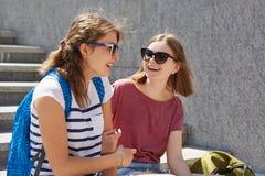 Δύο θηλυκοί φίλοι κάθονται στα βήματα υπαίθρια, έχουν τη ζωηρή επικοινωνία, φορούν τα γυαλιά ηλίου, περιστασιακή μπλούζα, φέρνουν στοκ εικόνες με δικαίωμα ελεύθερης χρήσης