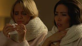 Δύο θηλυκοί φίλοι με τον πυρετό που βήχει και που φτερνίζεται, εποχιακό κρύο, υγειονομική περίθαλψη φιλμ μικρού μήκους