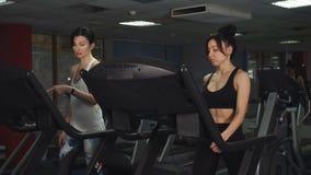 Δύο θηλυκοί φίλοι που τρέχουν treadmill Κατηγορίες στο κέντρο ικανότητας φιλμ μικρού μήκους