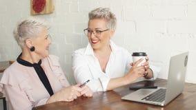 Δύο θηλυκό ανώτεροι συνάδελφοι που κάθεται το ένα δίπλα στο άλλο σε έναν καφέ απόθεμα βίντεο