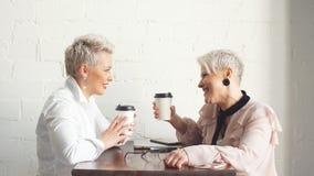 Δύο θηλυκό ανώτεροι συνάδελφοι που κάθεται το ένα δίπλα στο άλλο σε έναν καφέ φιλμ μικρού μήκους