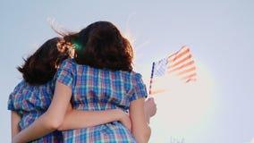 Δύο θηλυκά δίδυμα με μια αμερικανική σημαία σε ένα υπόβαθρο μπλε ουρανού υποστηρίξτε την όψη ανεξαρτησία ημέρας ανασκόπησης grung απόθεμα βίντεο