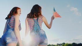 Δύο θηλυκά δίδυμα με μια αμερικανική σημαία σε ένα υπόβαθρο μπλε ουρανού υποστηρίξτε την όψη ανεξαρτησία ημέρας ανασκόπησης grung φιλμ μικρού μήκους