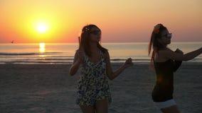 Δύο θηλυκοί έφηβοι στην παραλία με τα κεριά πυροτεχνημάτων στα χέρια τους στην ανατολή απόθεμα βίντεο