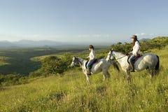 Δύο θηλυκοί αναβάτες πλατών αλόγου στην πλάτη αλόγου οδηγούν στο ηλιοβασίλεμα δεδομένου ότι κάποιος δείχνει την παράβλεψη της κοι Στοκ Εικόνα