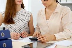 Δύο θηλυκοί λογιστές που βασίζονται στο εισόδημα υπολογιστών για την κινηματογράφηση σε πρώτο πλάνο χεριών ολοκλήρωσης φορολογική Στοκ Φωτογραφίες