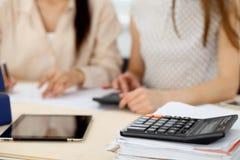 Δύο θηλυκοί λογιστές που βασίζονται στο εισόδημα υπολογιστών για την κινηματογράφηση σε πρώτο πλάνο χεριών ολοκλήρωσης φορολογική Στοκ Εικόνες