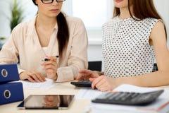 Δύο θηλυκοί λογιστές που βασίζονται στο εισόδημα υπολογιστών για την κινηματογράφηση σε πρώτο πλάνο χεριών ολοκλήρωσης φορολογική Στοκ φωτογραφία με δικαίωμα ελεύθερης χρήσης