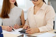 Δύο θηλυκοί λογιστές που βασίζονται στο εισόδημα υπολογιστών για την κινηματογράφηση σε πρώτο πλάνο χεριών ολοκλήρωσης φορολογική Στοκ Εικόνα