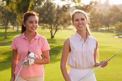 Δύο θηλυκοί παίκτες γκολφ που περπατούν κατά μήκος των φέρνοντας λεσχών στενών διόδων Στοκ Εικόνα