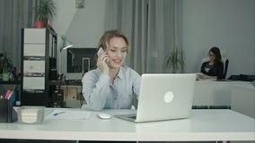 Δύο θηλυκοί συνάδελφοι που απασχολούνται μαζί να απαντήσει στα τηλεφωνήματα στο γραφείο απόθεμα βίντεο